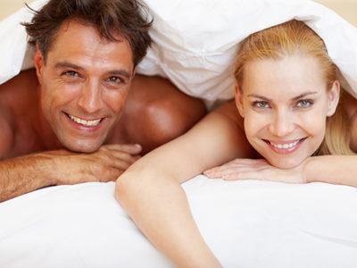 """Portrait of happy, beautiful couple lying under bedsheet"""